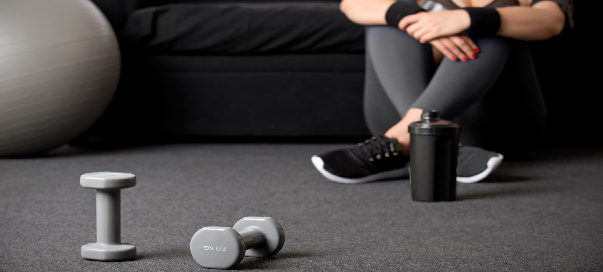 Woman in exercise gear sitting in front of couch with balance ball and dumbbells on carpet