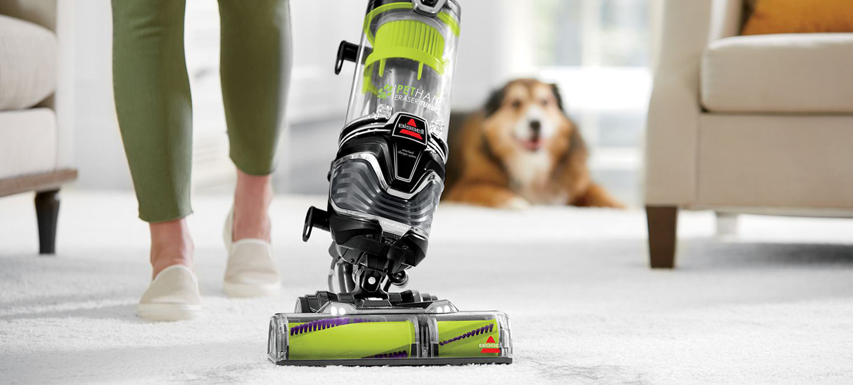 Green vacuum cleaner on carpet with blurred dog in background