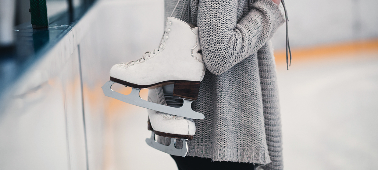 Shoulders-down image of a woman in a grey sweater standing on an ice rink with a pair of white figure skates hanging over her shoulder
