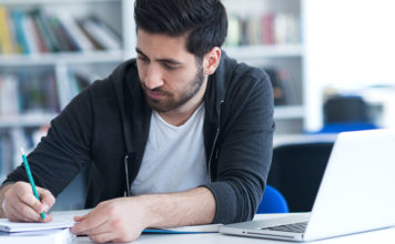 Male student studying with a laptop