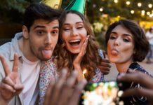 Two women and one man in party hats posing for a picture