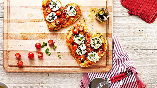 Heart-shaped margherita pizzas served on a wooden cutting board.