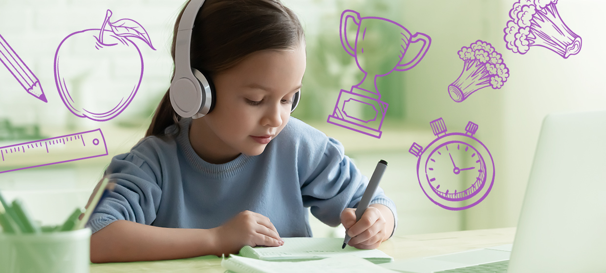 Student sitting at table, wearing white headphones; she is working on homework from home.