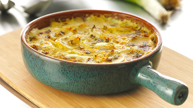 Skinny scalloped potatoes in a green pot