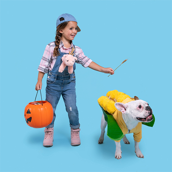 Young girl and dog dressed in DIY farmer and corn on the cob costumes
