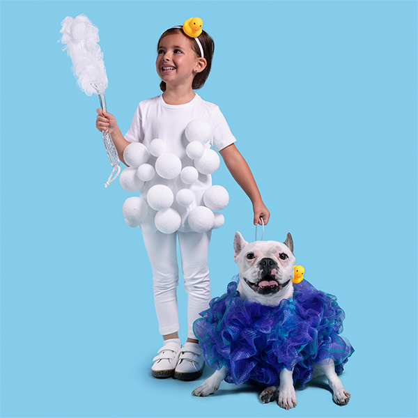 Young girl and dog dressed in DIY bubble bath and loofah costumes