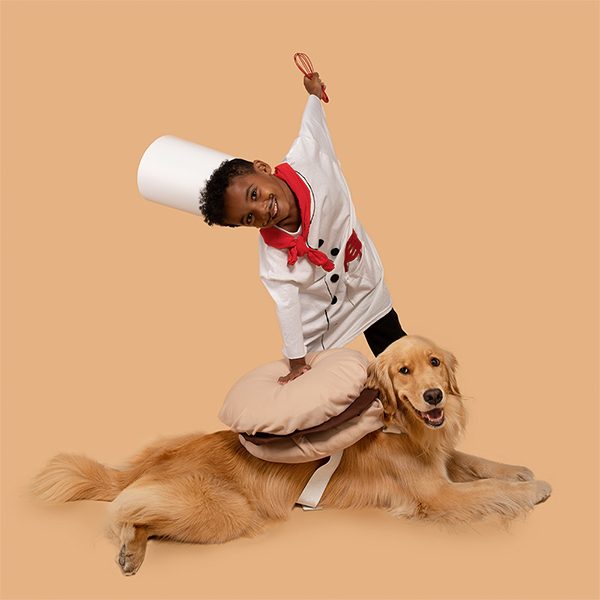 Young boy and dog dressed in DIY chef and macaron costumes