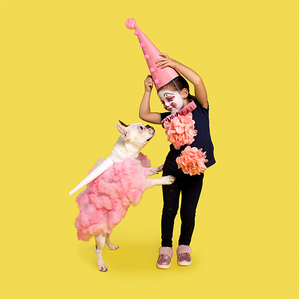 Young girl and dog dressed in DIY clown and cotton candy costumes