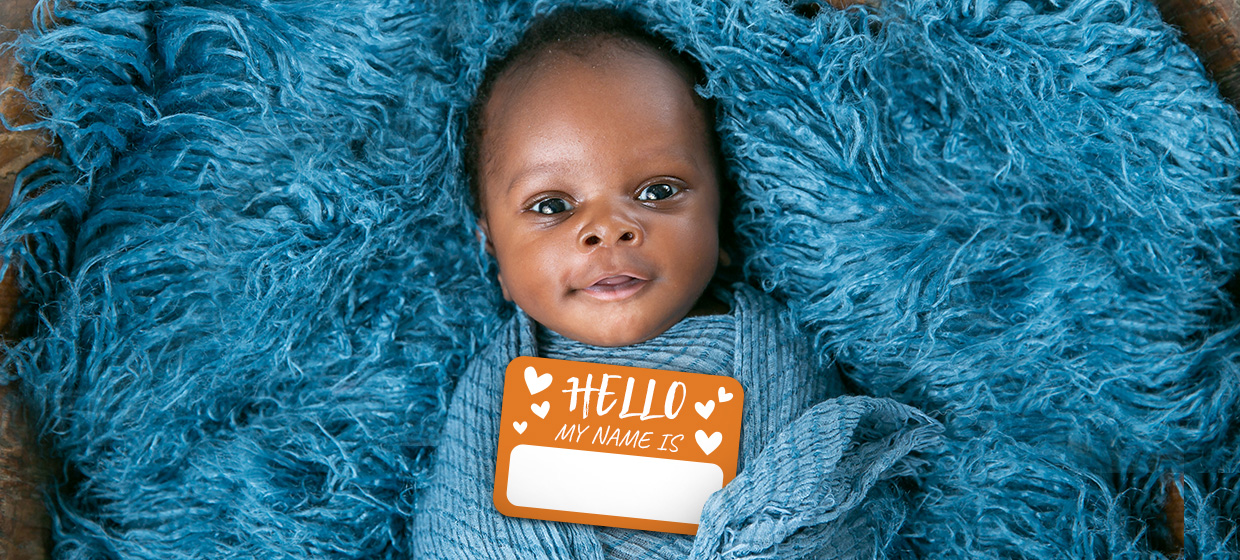 """Black baby wrapped in blue wears a tag that says """"Hello, My Name Is"""" before parents do baby name selection"""