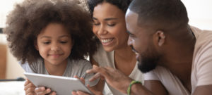 Mom, dad and daughter look at an iPad or tablet