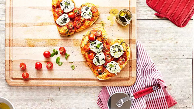 mint, tomato and goat cheese pizzas on cutting board