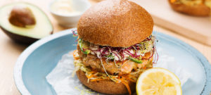 avocado salmon burger with sprouts and carrot slaw
