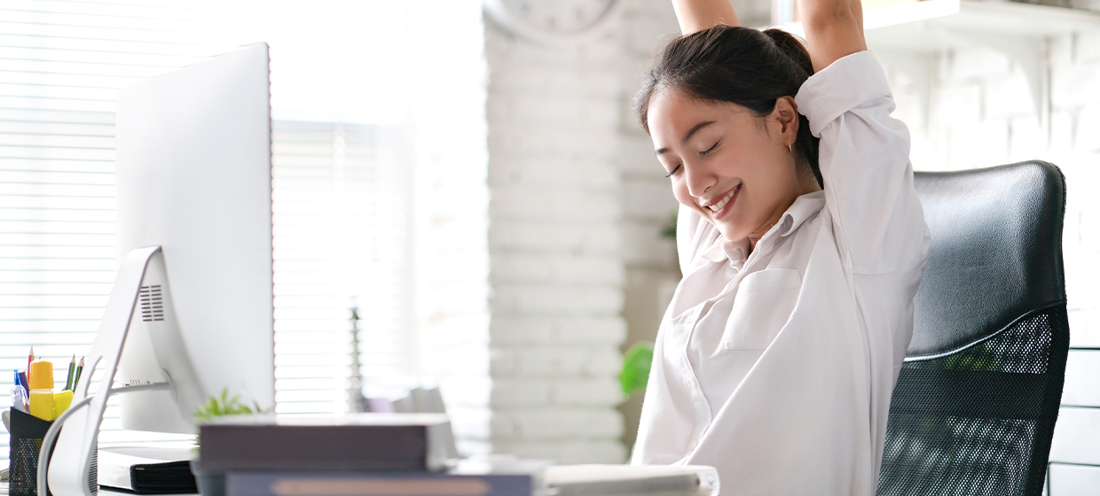 woman stretching comfortably in her home office